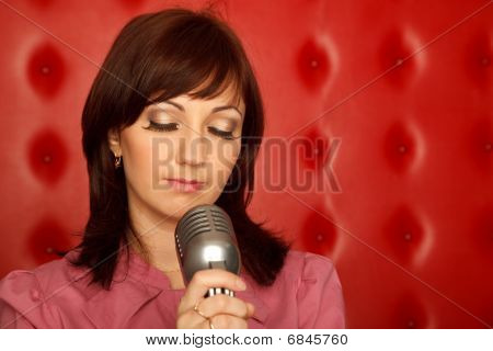 Portrait of girl in red shirt with microphone on rack against red wall. Horizontal format