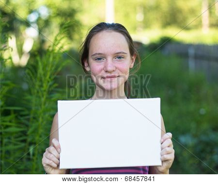 Cute  teengirl holding clean white sheet paper, outdoors (banner for your message)