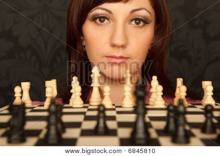 Portrait of girl in red shirt with chessboard. Horizontal format. Close-up.