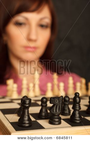 Girl with the sad looks on the chessboard. Close-up. Blur background.