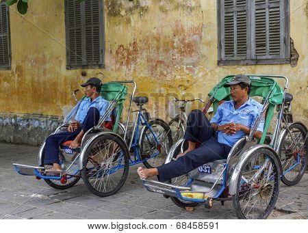 Two Rickshaw Drivers Wait For Customers.