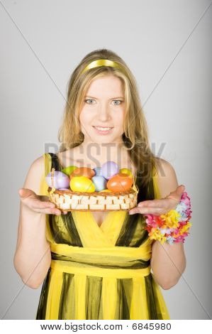 Young beautiful spring woman holding lots of easter eggs