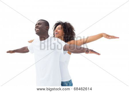 Casual couple standing with arms outstretched on white background