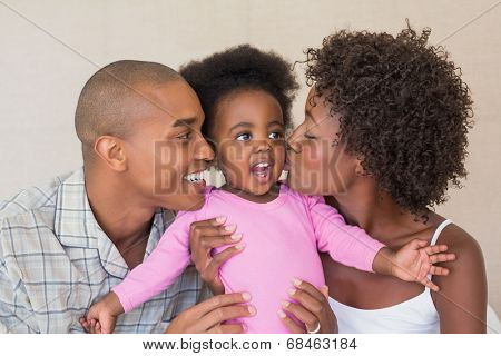 Happy parents and baby girl on bed together at home in the bedroom