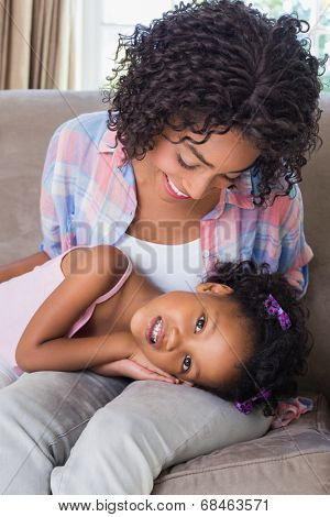 Cute daughter lying across mothers lap at home in the living room