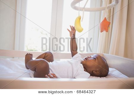Adorable baby boy lying in his crib playing with mobile at home in the bedroom