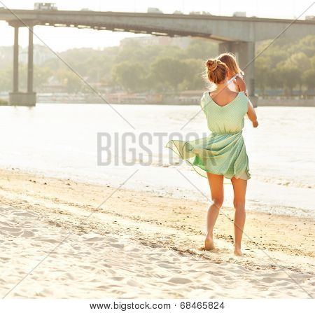 Happy Mother Holding Her Bay Girl At Beach