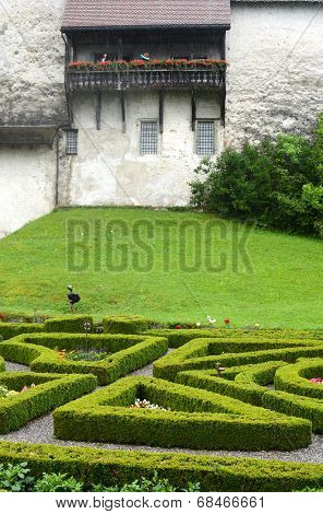 GRUYERES, SWITZERLAND - JULY 8, 2014: Garden and balcony at Gruyeres Castle. Located in the medieval town of Gruyeres and built between 1270 & 1282, it is one of the most famous castles in Switzerland