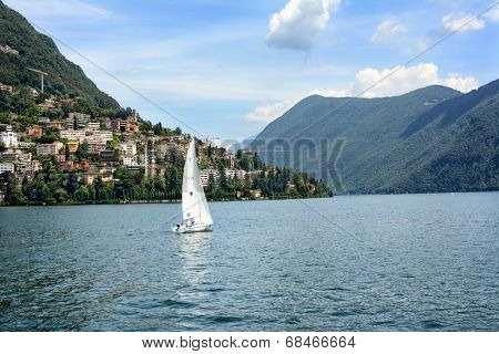 LUGANO, SWITZERLAND - JULY 5, 2014: Sailboat on Lake Lugano, with Mt. Bre and Castagnola in the background. The lake is a glacial lake situated on the border between Switzerland and Italy.