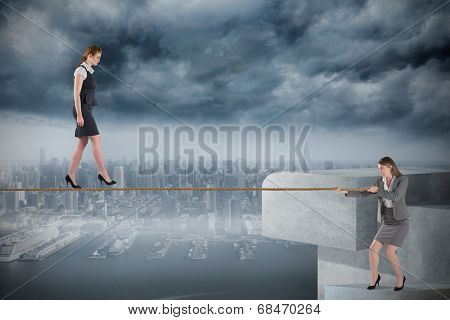 Young businesswoman pulling a tightrope for business woman against coastline and city