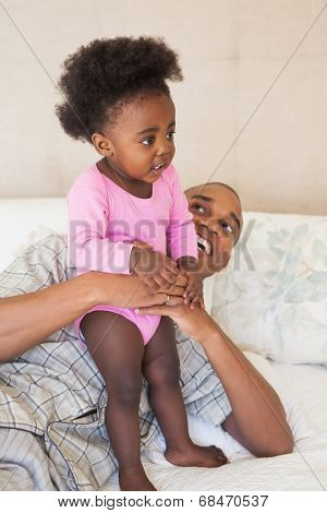 Father and baby girl lying on bed together at home in the bedroom