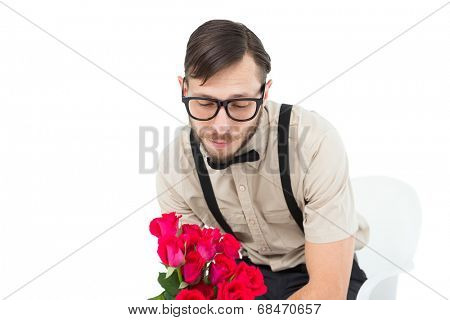 Geeky heartbroken hipster holding roses on white background
