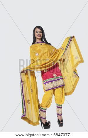 Full length of an Indian woman in salwar kameez standing over gray background
