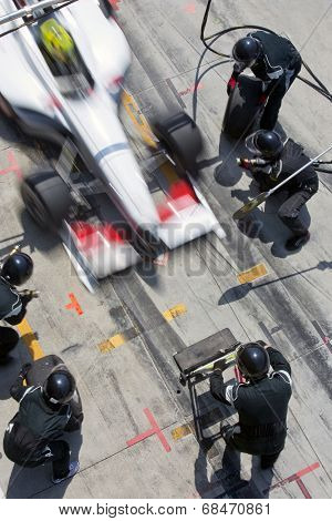 Professional pit crew ready for action as their team's race car arrives in the pit lane during a pitsstop of a car race, concept of ultimate teamwork