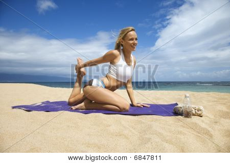 Attractive Young Woman Doing Yoga On Beach