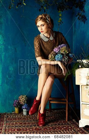 portrait of a beautiful woman with red hair in curly braided hairstyle. wearing a romantic lace dress with red boots on grunge blue background