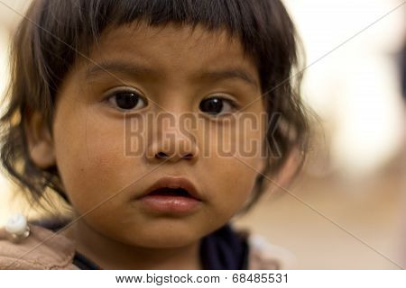 Sucre, Bolivia - January 17, 2012: A Young Indigenous Boy Faces The Camera While Playing In The Stre
