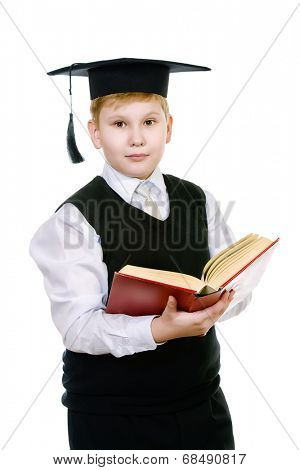 Serious schoolboy in academic hat standing with a book. Isolated over white.
