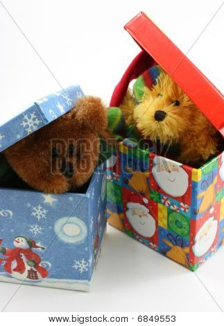 Stuffed bear toys peaking out of Christmas boxes