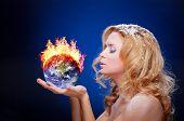 stock photo of hemisphere  - Frozen girl holding burning earth globe  - JPG