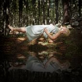 foto of levitation  - Levitating woman in the forest above water - JPG
