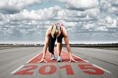 image of kneeling  - Female sprinter waiting for the start on an airport runway - JPG