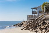 stock photo of beach-house  - A nice house on the beach with walkway into the sand and a suspension bridge in the background - JPG