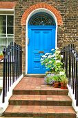 picture of victorian houses  - London entrance to a house with flower beds full of flowers - JPG