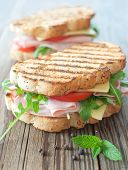 image of deli  - Grilled deli sandwiches with ham and cheese on top of a chopping board - JPG