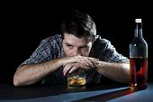 stock photo of alcohol abuse  - grunge alcoholic man drunk at the table with whiskey glass in alcohol addiction and alcoholism concept - JPG
