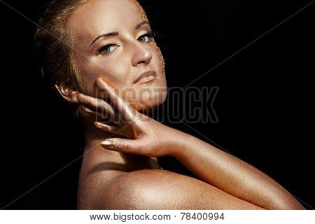 girl with golden bodyart on a black background
