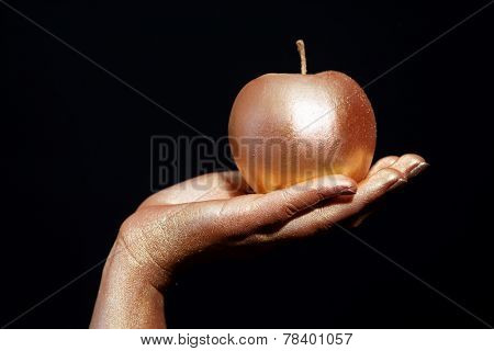 Female hand with gold bodypainting holding an apple on a black background