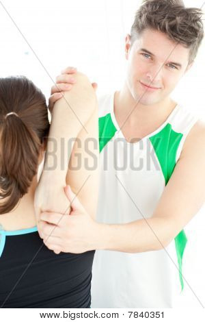 Smiling Physical Therapist Checking A Woman's Shoulder