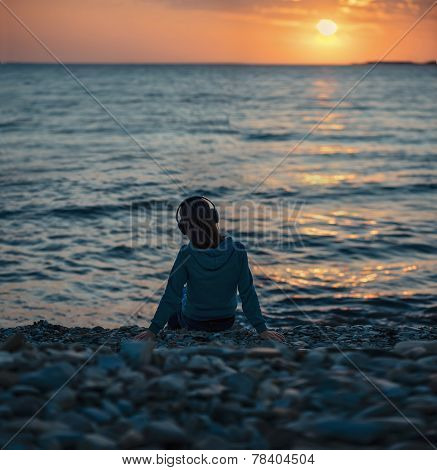 Girl In Headphones Sitting On Beach On Sunset