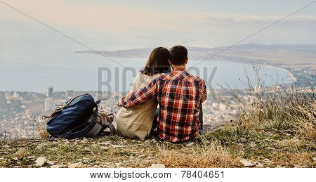 Couple In Love Sitting On Hill And Looking At The City