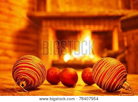 Cozy Christmas eve at home, beautiful red glass balls on the floor on fireplace background, luxury Christmas tree decoration