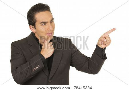 handsome young man wearing a suit posing pointing to the side