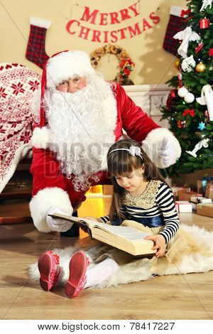 Santa Claus reading book with little cute girl near  fireplace and Christmas tree at home