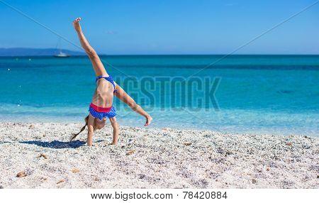 Adorable little girl making wheel on tropical white sandy beach