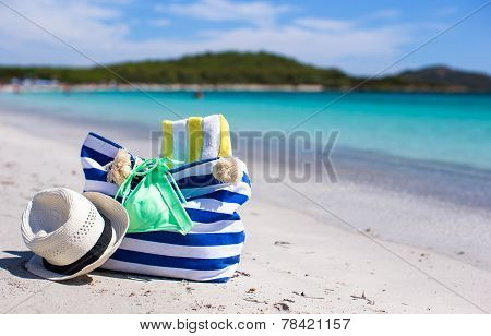 Summer accessories, swimsuit, sunglasses, bag and hat on white beach