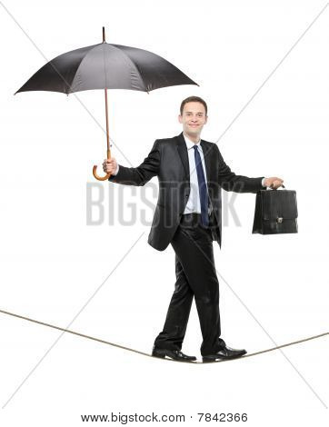 A business person holding an umbrella and a briefcase walking on a tightrope