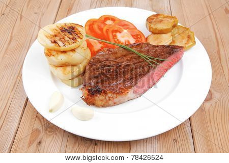 meat savory : grilled beef fillet mignon served on white plate with tomatoes and potatoes on wooden table