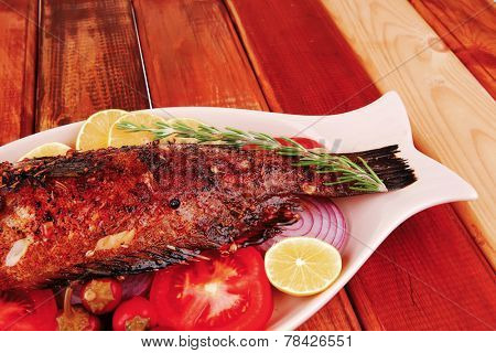 savory: whole fryed sunfish over wood with tomatoes lemons and peppers