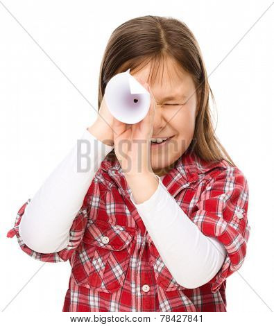 Cute little girl is looking through spyglass made of paper, isolated over white