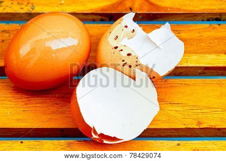 Eggs And Egg Shells On The Wooden Floor.