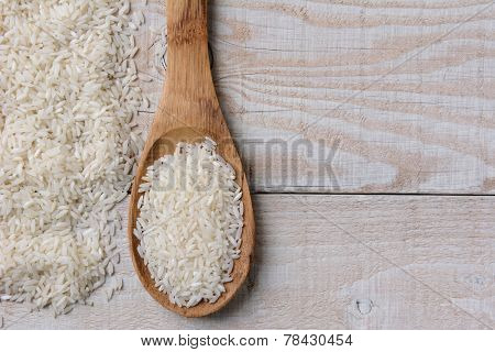 Closeup of a spoonful of uncooked rice and grains scattered on a rustic whitewashed wooden table. Horizontal format with copy space.