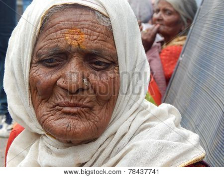 Portrait of Indian woman begging on a busy road