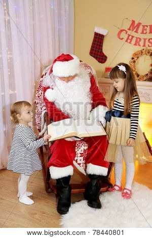 Santa Claus reading book with two little cute girls near  fireplace and Christmas tree at home