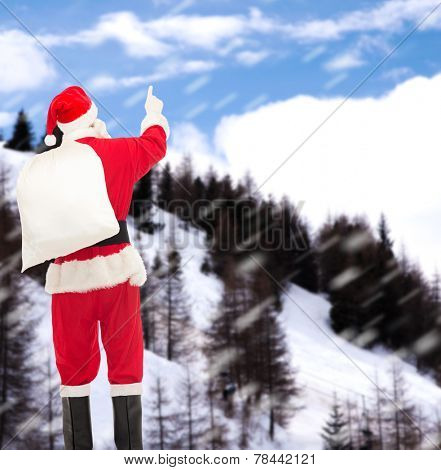 christmas, holidays and people concept - man in costume of santa claus with bag pointing finger from back over snowy mountains background