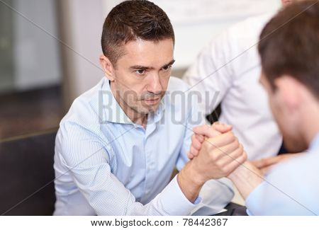 business, people, crisis and confrontation concept - businessmen arm wrestling in office